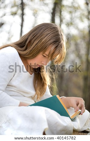 girl reads book in the autumn park