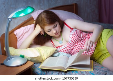 A girl reads a book in bed at night
