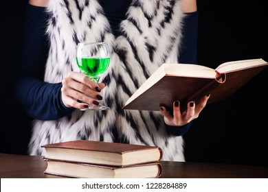 Girl reads book and drinks absinthe or green fairy drink in dark room. Stimulating drink for artists inspiration concept image. Close up, selective focus