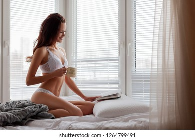 Girl Reads a Book and Drinks aromatic fresh Coffee in a cozy Bed in the Morning by the Window. Sexy Woman in white lace underwear sitting in Bed. Girl Resting in her New Apartment enjoying a Morning