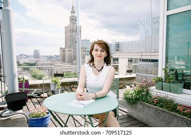 The girl reads a book overlooking the Palace of Culture in Warsaw, a business woman. The lady sits at the table, drinks coffee and relaxes from work. Working break. Fine day.