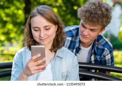 A girl reads messages on the phone. The guy is spying on his back. Summer in nature. The concept of mistrust peeping at the interlocutor.
