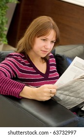 The girl reads the newspaper in an armchair