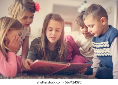 Girl reads a story to her sisters and brother.