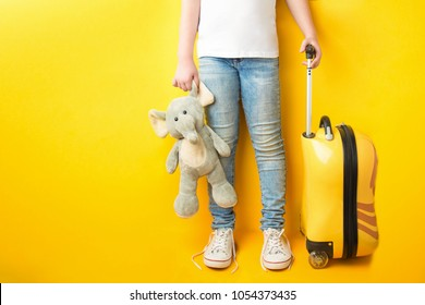 girl  ready for the journey. legs of the girl in casual clothing  in jeans and a white T-shirt with a toy in her hand and a suitcase on a yellow background. Girl packs her bags. Dreams of trip