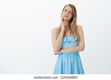 Girl recalling conversation starting overthink, getting triggered. Thoughtful hesitant and focused young attractive woman with blond hair in blue dress looking at upper left corner, thinking