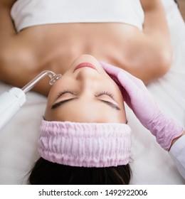 Girl receiving darsonval procedure electric massage at beauty salon. Hardware cosmetology. Selective focus.