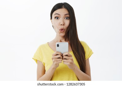 Girl receiving intriguing offer via message folding lips in wow sound gazing curiously and interested at camera holding smartphone being delighted and surprised with cool new feautures of phone app