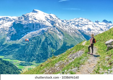 A girl with a red backpack admiring the scenery of the Alpine mountains. Landscape of the Swiss Alps.