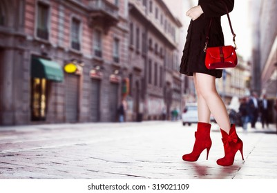 A girl with red bag and red boots in the street. Black coat.Beautiful legs in autumn winter time.