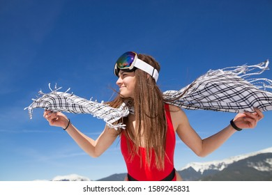 girl in a red bathing suit and glasses for a snowboard on the hillside. fitness model in a winter resort