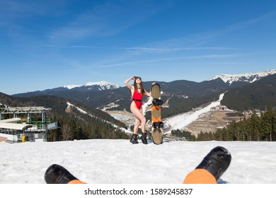 girl in a red bathing suit and glasses for a snowboard on the hillside. fitness model at a winter resort. Girl holds snowboard