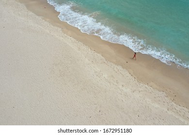 girl in a red bathing suit walks along the beach along the coastline