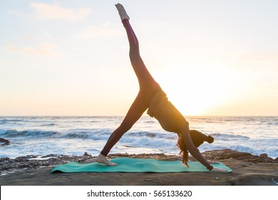 Girl in red bottoms, gray jacket and black hat doing yoga on a green yoga mat near the ocean at sunset