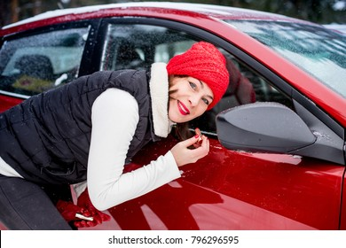 Girl in a red cap and warm jacket paints her lips near mirror of red car in a cold day