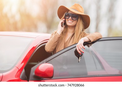 Girl in a red car in glasses