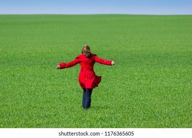 Girl in red cloak on green spring field