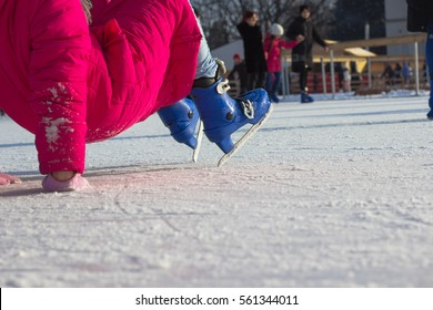 Girl in a red coat and on  blue figured skates fell on the ice rink