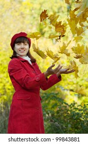 Girl in red coat throw up maple leaves