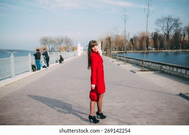 girl in red coat walking by the lake