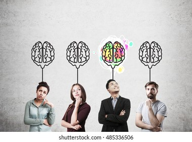 Girl in red dress, African American girl, guy in T-shirt and Asian man standing near concrete wall with brain sketches. Concept of teamwork.