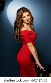 girl in red dress with curly hair on blue background