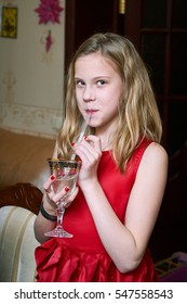 Girl in a red dress drinking champagne for children from the cocktail tube