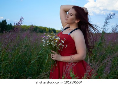 girl in a red dress in a field with a bouquet of daisies
