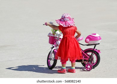 girl in red dress and hat try to ride pink kid bike on concrete floor background.