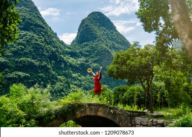 Girl in red dress jumping on the old stone bridge in Yangshuo