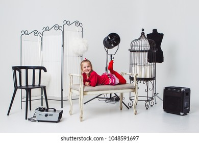 the girl in the red dress lies on the sofa in the photo Studio on the cyclorama among various interior items.