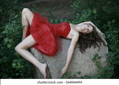 girl in red dress lying on the ground in nature, seductive in green forest