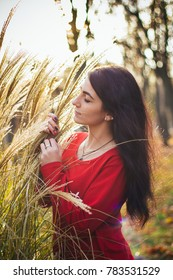 girl in a red dress. girl on the background of leaves. spike autumn photo. brunette.