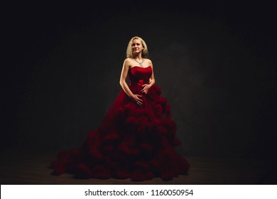 Girl in a red dress on a dark background. Bordeaux Dress Cloud. Blonde girl