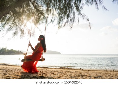 girl in a red dress on a swing among tropical palm trees in Thailand at sunset