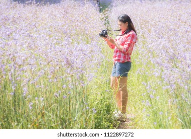A girl in red dress is photographed in the middle of a purple flower field. She looks happy.