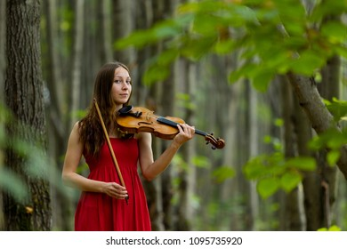 The girl in a red dress playing the violin in the woods, soft light