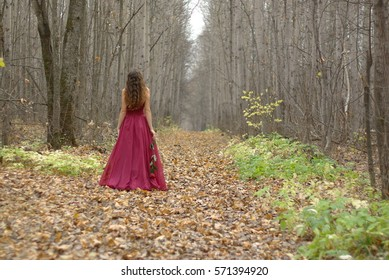 Girl in red dress with a rose walking in the autumn forest