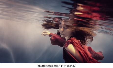 Girl in a red dress under water
