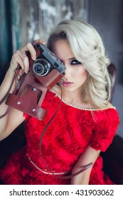 Girl in red dress with vintage retro camera