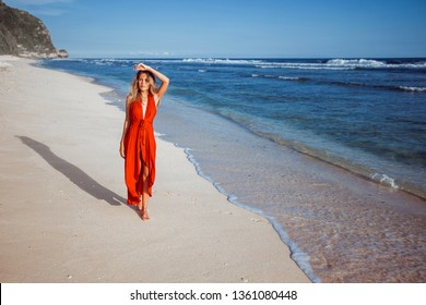 Girl in a red dress walking on the ocean, on the beach with white sand