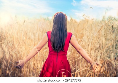 girl in red dress walking on wheat field