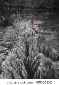A girl in red dress was walking on a sandstone slab that had been washed down by rain. Show the obstacles to face.
