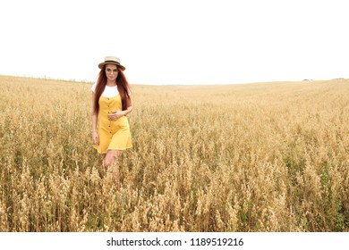 girl with red hair in the autumn field of wheat