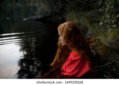 Girl with red hair in a red dress, Sits in the water. Art photo.