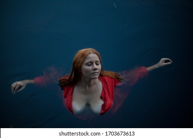 Girl with red hair in a red dress, Sits in the water. Art photo.The woman is not naked.