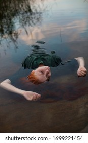 The girl with red hair and in a green dress lies completely in the water, only her face is visible. Art photo.