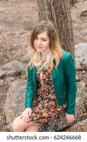 the girl with red hair and green jacket walks and resting , portrait . standing near the tree , her eyes with tears and a smile on your face , plain