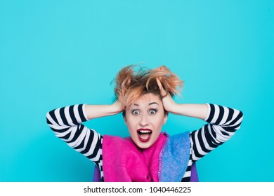 Girl with red hair holding her head shouting. Stress and hysterical. negative emotions. Studio shot. Blue  background