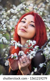 The girl with red hair inhales the fragrance of the flowers of the tree. Outdoor. Spring.